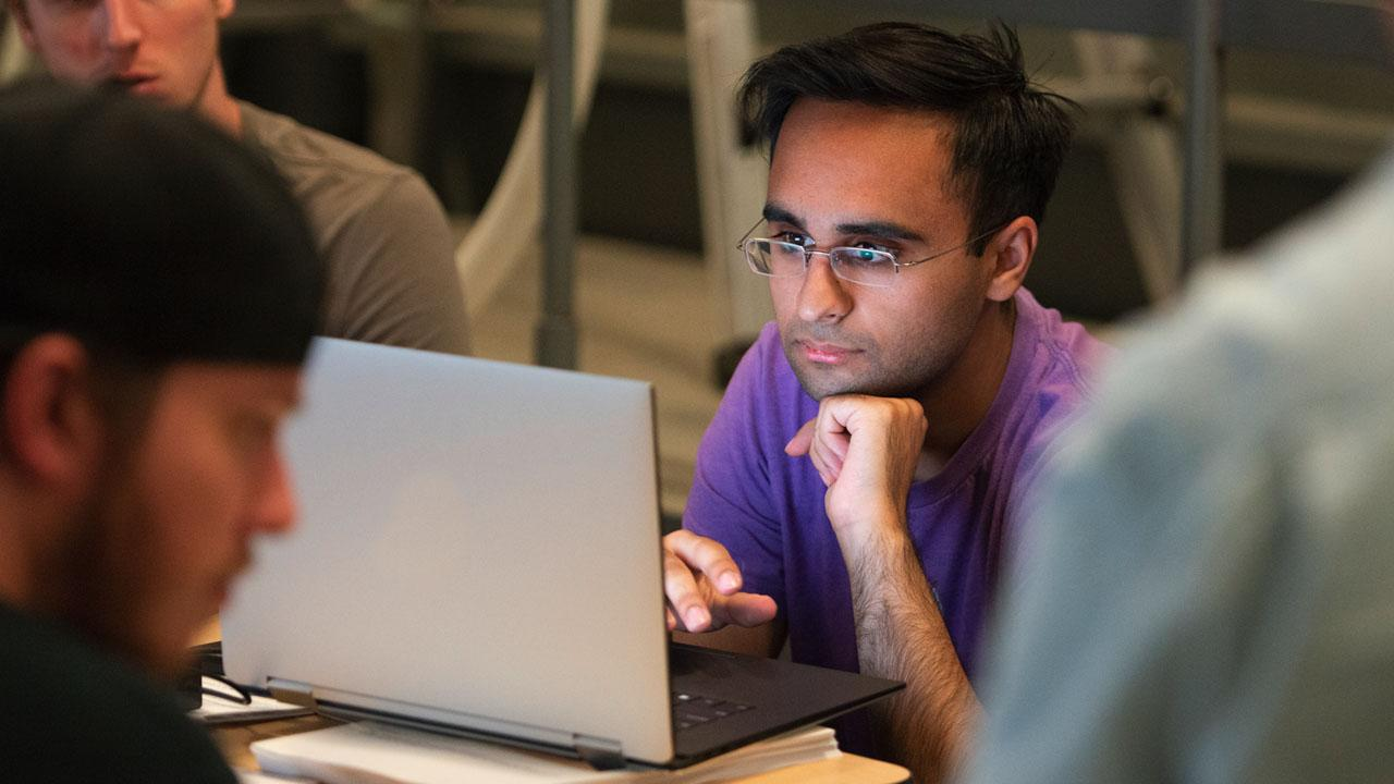 student looking intently at laptop